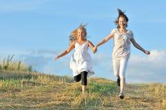 Två flickor som kör över fältet Royaltyfri Bild