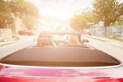 Två flickor som kör den konvertibla bilen Royaltyfria Bilder