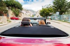 Två flickor som kör en konvertibel bil Royaltyfria Bilder