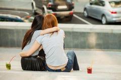 Två flickor som kramar, och drinkförkylningcoctailar Royaltyfri Foto