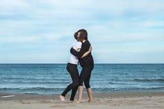 Två flickor som kramar på stranden royaltyfri bild