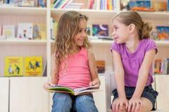 Två flickor som läser en bok i arkivet och skrattet Fotografering för Bildbyråer
