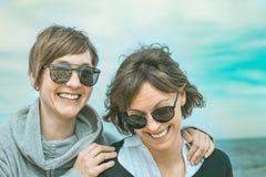 Två flickor som ler och har gyckel på stranden Sund och gladlynt livsstil royaltyfri foto