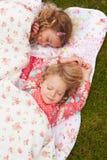 Två flickor som ligger under filten på campa ferie royaltyfria foton