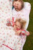 Två flickor som ligger under filten på campa ferie arkivbild