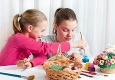 Två flickor som målar påskägg arkivfoto