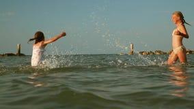 Två flickor som plaskar vatten arkivfilmer