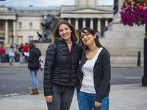 Två flickor som poserar för foto på Trafalgar Square i London Royaltyfri Bild