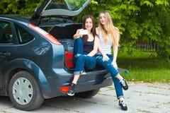 Två flickor som poserar i bil Fotografering för Bildbyråer