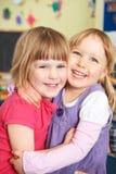 Två flickor som Pre kramar på skolan arkivbild