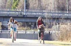 Två flickor som rider en cykel i parkera Royaltyfria Foton