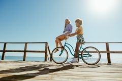 Två flickor som rider på en cykel på stranden fotografering för bildbyråer