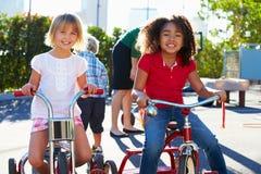 Två flickor som rider trehjulingar i lekplats Arkivfoto