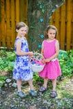 Två flickor som rymmer en påskkorg i en trädgård Royaltyfria Bilder