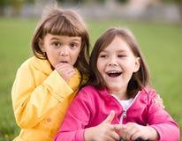 Två flickor som rymmer framsidan i misstro Royaltyfri Bild