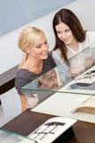 Två flickor som ser fönsterfallet med smycken arkivbilder