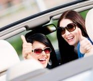 Två flickor som sitter i bilen och tummar upp Arkivfoton
