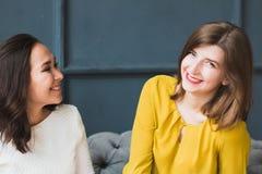 Två flickor som sitter på soffan och skrattet Royaltyfria Foton