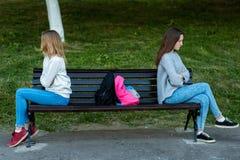 Två flickor som skolflickan grälade i sommaren parkerar in De sitter på en bänk Begreppet av konflikten, skandal, problem in royaltyfria foton