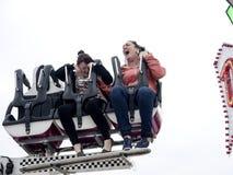 Två flickor som skriker på en nöjesplatsritt Arkivfoto