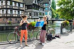 Två flickor som spelar flöjten på gatan i Strasbourg Arkivbilder