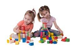 Två flickor som spelar med färgrikt märkes- sammanträde royaltyfria foton
