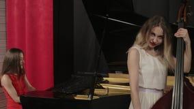 Två flickor som spelar musikinstrument Piano och doublebass stock video