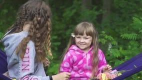 Två flickor som spelar på hängmattan arkivfilmer