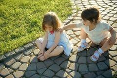 Två flickor som spelar på solig sommardag utomhus royaltyfri fotografi