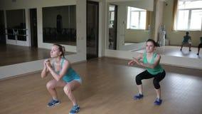 Två flickor som squatting i idrottshallen stock video