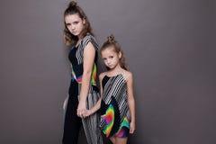 Två flickor som systrar sid - förbi - sid på en grå bakgrund Royaltyfri Bild