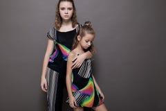 Två flickor som systrar sid - förbi - sid på en grå bakgrund Royaltyfria Bilder