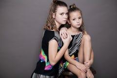 Två flickor som systrar sid - förbi - sid på en grå bakgrund Royaltyfri Fotografi