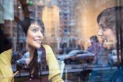 Två flickor som talar i ett kafé Arkivbild