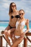 Två flickor som talar i ett kafé nära havet Fotografering för Bildbyråer