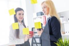 Två flickor som talar i kontoret Flickor är en dialog nära ett genomskinligt bräde med klistermärkear arkivbilder