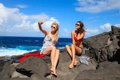 Två flickor som tar fotoet på stranden i sommarferier och vacat Arkivfoto