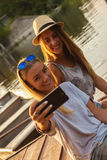 Två flickor som tar Selfie nära floden Royaltyfria Bilder
