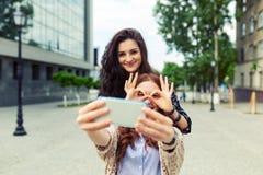 Två flickor som tillsammans gör rolig selfie på gatan och att ha gyckel fotografering för bildbyråer
