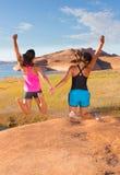 Två flickor som tillsammans hoppar Royaltyfri Foto