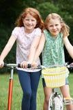 Två flickor som tillsammans rider cykeln och sparkcykeln Royaltyfria Bilder