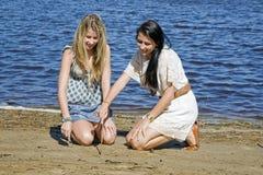 Två flickor som writning med sticken i sand vid liten vik Royaltyfri Bild