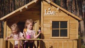 Två flickor spelar i en treehouse stock video