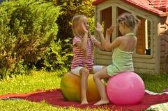 Två flickor spelar i trädgården Arkivfoton