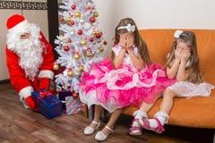 Två flickor stängde ögon med hans händer, tills Santa Claus satte gåvor under julgranen Royaltyfri Bild