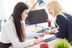 Två flickor står i kontoret böjde över nära tabellen och arbetet med dokument arkivbilder