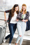 Två flickor står med resväskor på flygplatsen och att se minnestavlan En tur med vänner Fotografering för Bildbyråer