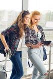 Två flickor står med resväskor på flygplatsen och att se minnestavlan En tur med vänner royaltyfri bild
