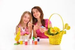 Två flickor - systrar målade påskägg och gyckel Royaltyfria Bilder