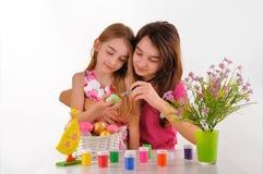 Två flickor - systrar målade påskägg. på vitbakgrund Arkivbild